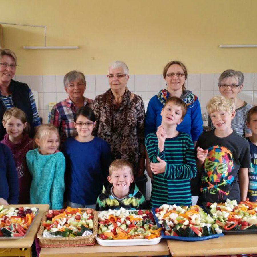 Ein Tich voller Rohkost-Nahrung und weiteres gesundes Essen. Dahinter stehen die Kinder der Grundschule Bötersen vor den Erwachsenen Initiatoren.