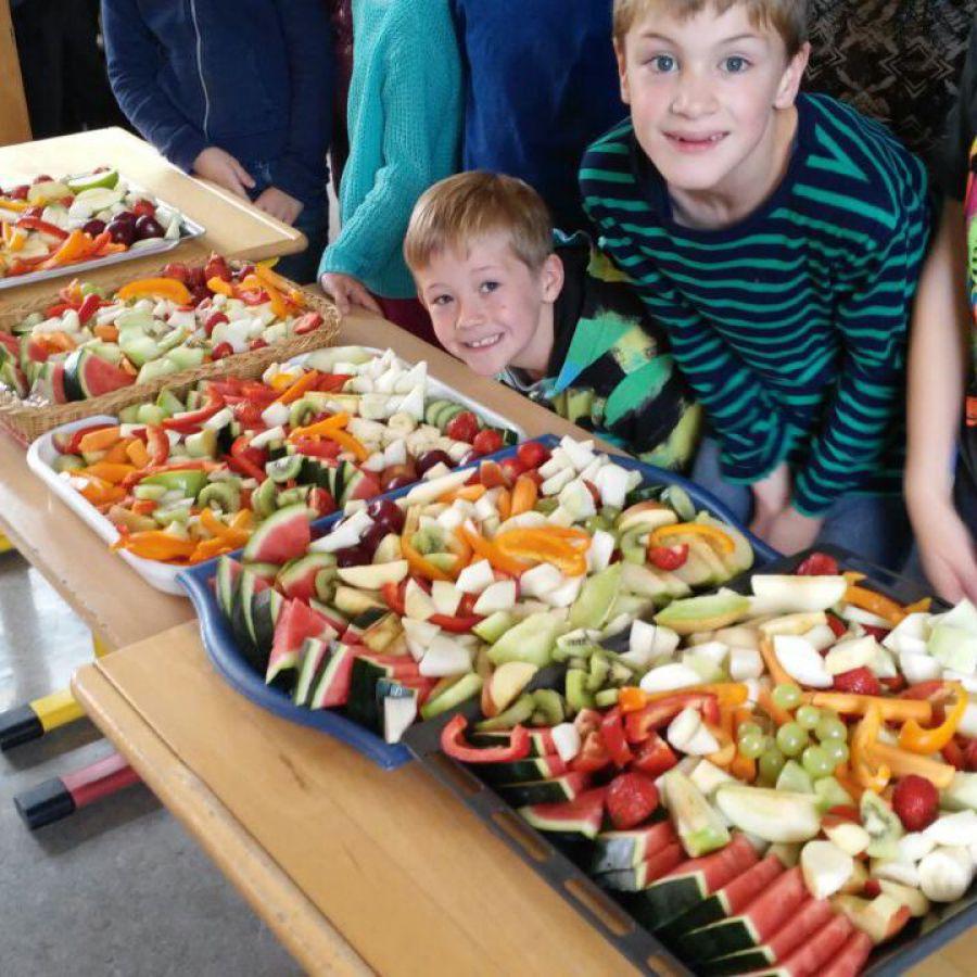 Ein Tisch voller Rohkost und Obst. Im Hintergrund Schüler der Grundschule Bötersen.