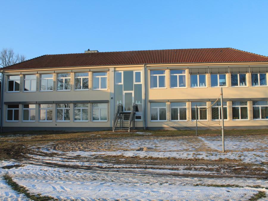 EinBild der Rückseite der Grundschule von Bötersen. Das Gebäude ist beige