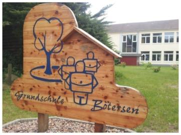 """Ein Holzschild auf dem mit bleuer Schrift der Schriftzug """"Grundschule Bötersen"""" mit dem Logo aufgemalt wurde."""